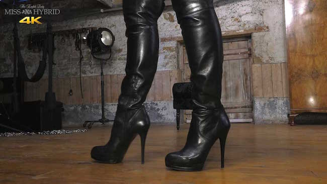 Miss Hybrid leather thigh boots, pantyhose and big tits in the dungeon playing with her glass dildo.